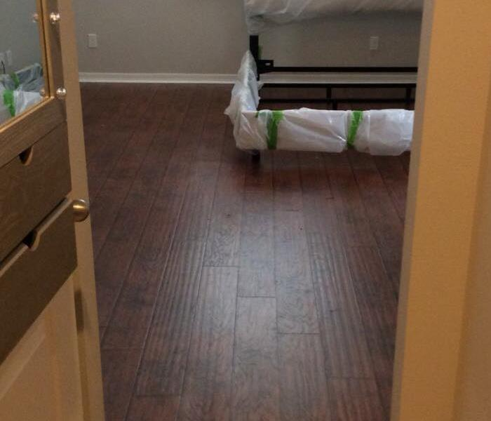 Hardwood flooring in bedroom with bed frame