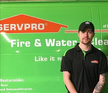 Male crew member standing in front of a SERVPRO van